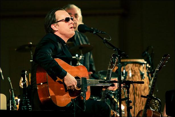 image of Joe Bonamassa Live At Carnegie Hall, sitting playing an acoustic guitar