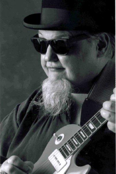 black and white image of blues singer songwriter Bryan Lee holding a guitar