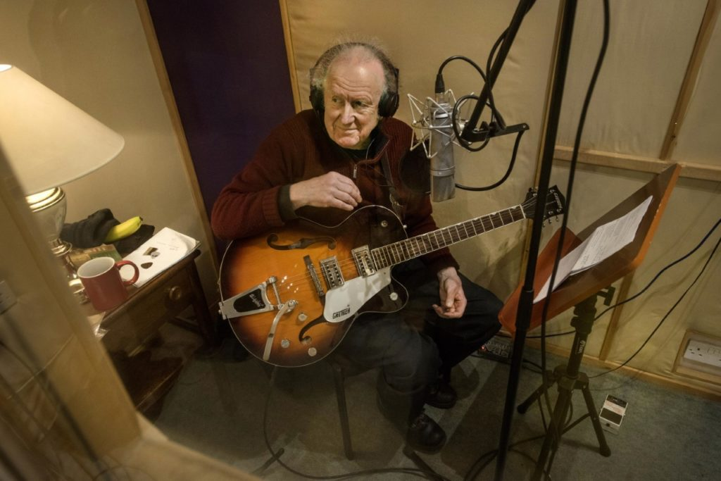 image of seamus mcgarvey sitting with a guitar in the studio by douglas robertson